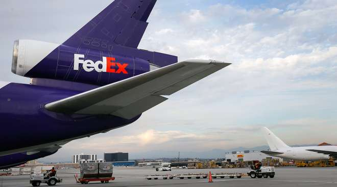 Employees drive carts on the tarmac past a cargo plane waiting to be loaded with shipments at the FedEx Corp. distribution hub at Los Angeles International Airport (LAX) in Los Angeles.