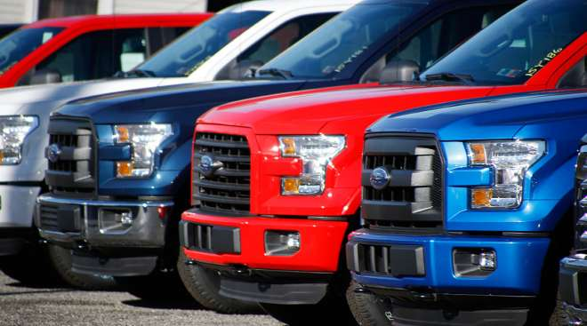 Row of Ford F-150 pickup trucks at a dealer lot