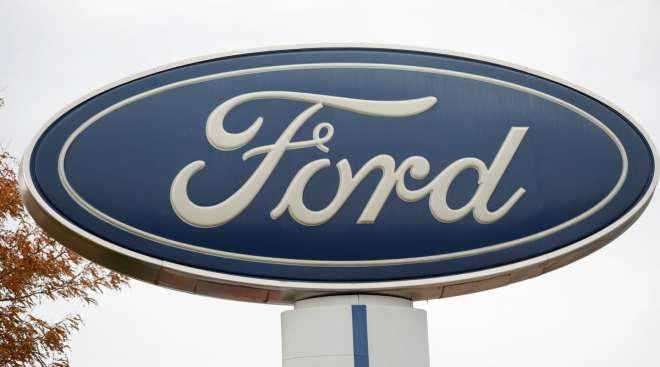 The Ford company logo stands over a row of vehicles in a Colorado dealership.