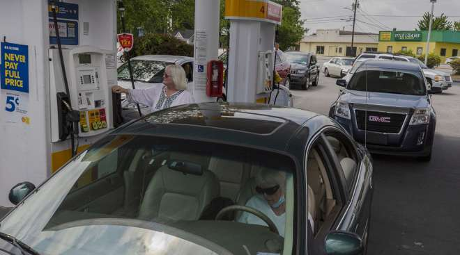 People fill vehicles with fuel at a Royal Dutch Shell gas station in Sumter, S.C.