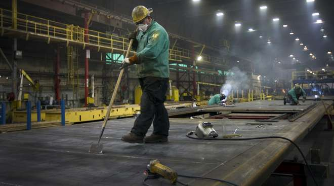 A welder works on sides for refrigerated rail cars at the Gunderson Rail Car Plant in Portland, Ore.