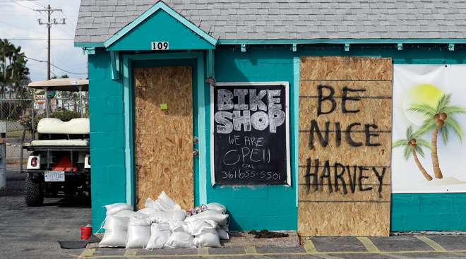 "A sign reading ""Be Nice Harvey"" was left behind on a boarded up business, Thursday, Aug. 24, 2017, in Port Aransas, Texas. Port Aransas is under a mandatory evacuation for Hurricane Harvey."