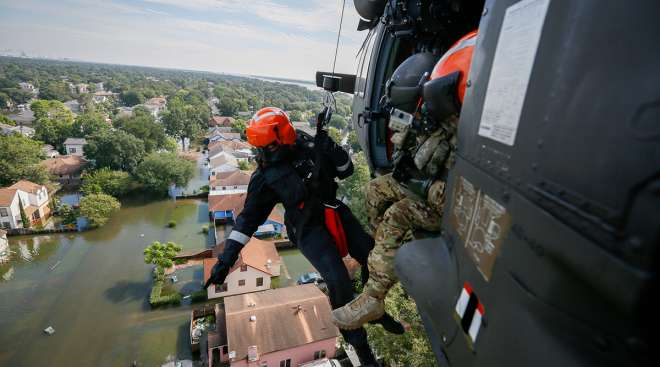 Brian Archibald, a rescue specialist assigned to the South Carolina Helicopter Aquatic Rescue Team Delta in McEntire Joint National Guard Base, S.C., points to a someone who may need help on Aug. 31, 2017 in Port Arthur, Texas.