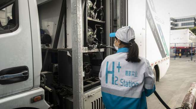 An attendant fills a truck with compressed hydrogen at a filling station in Shanghai.