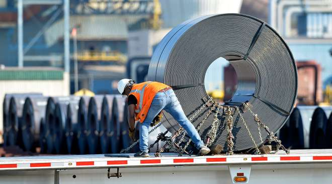 A truck driver chains down a roll of steel to his flatbed at the NUCOR Steel Gallatin plant in Ghent, Ky.