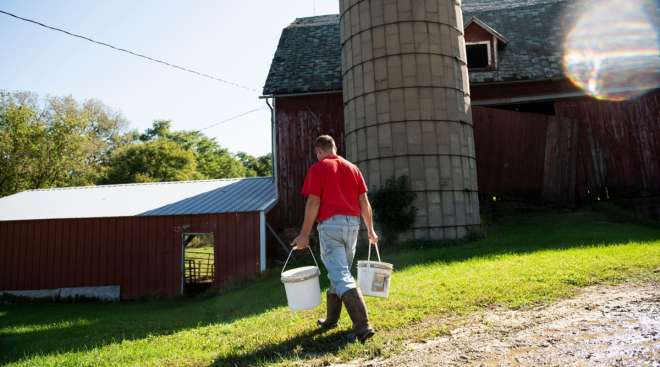 A farmer carries buckets on a dairy farm in Lancaster, Wis. (Lauren Justice/Bloomberg News)