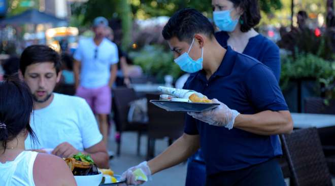A waiter wearing protective equipment serves food.