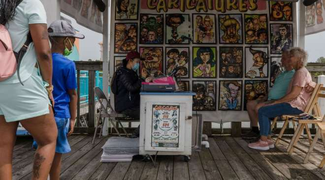 A caricature artist draws the image of a couple in Myrtle Beach, S.C. (Micah Green/Bloomberg News)