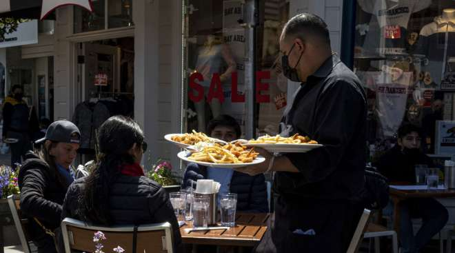 A worker serves food at a restaurant on Pier 39 in San Francisco. (David Paul Morris/Bloomberg News)