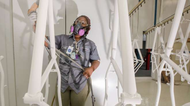 An employee coats bicycle frames with powder paint in South Carolina. (Micah Green/Bloomberg News)