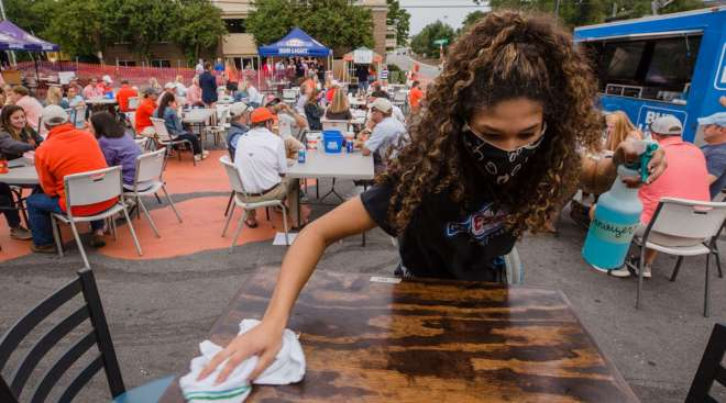 A server cleans a table in an outdoor area at a restaurant in Clemson, S.C.