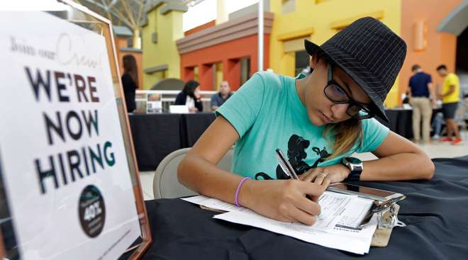 Woman filling out job application next to Help Wanted sign