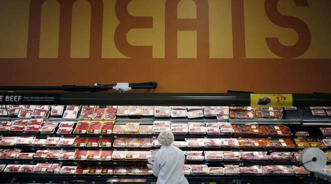 An employee restocks shelves in the meat section at a Kroger Co. supermarket in Louisville, Ky.