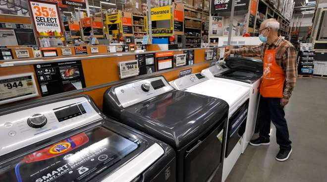 Javad Memarzadeh dusts washers on display in a Home Depot location in Boston on Oct. 29.