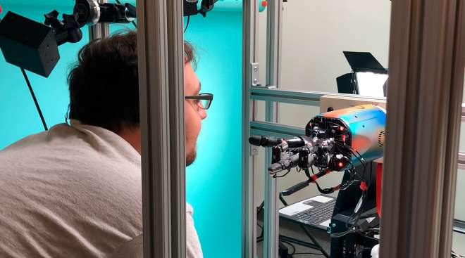 OpenAI researcher Jonas Schneider examines the research lab's robotic hand