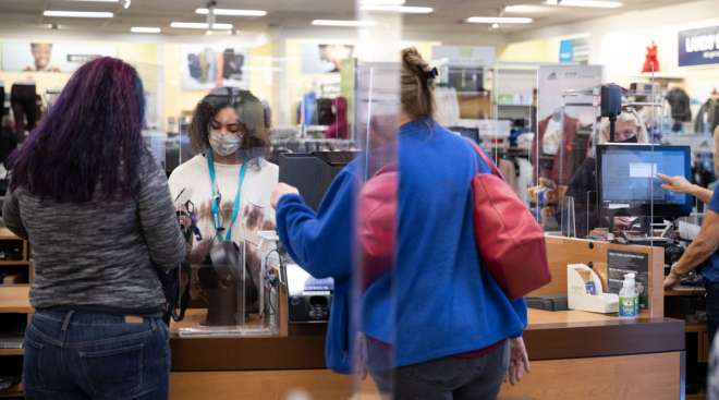 An employee wearing a protective mask assists customers at a department store in Georgia.