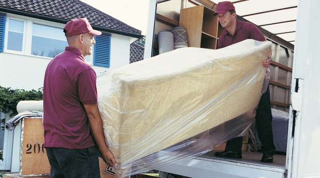 Men load sofa into a moving truck