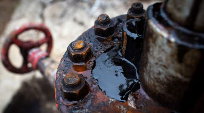 Thick black oil sits on the pipe work fitting of an oil pumping jack. (Andrey Rudakov/Bloomberg News)