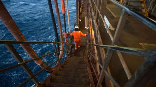 An employee walks down stairs at the Armada gas condensate platform.