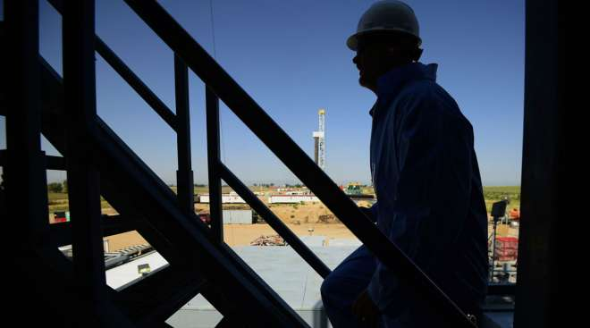 The silhouette of a contractor is seen walking up stairs at an oil rig site in Colorado.