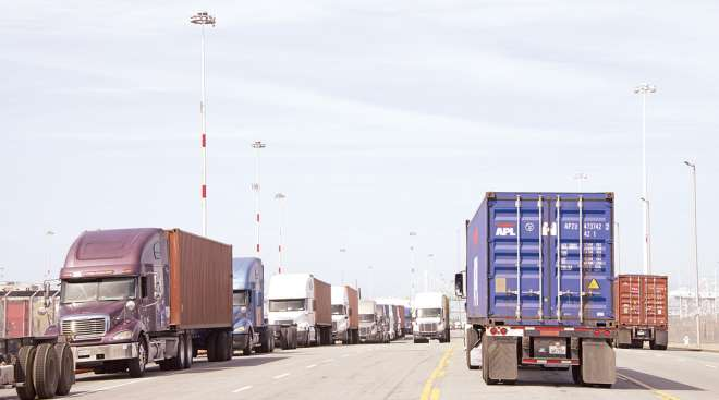 trucks line Middle Harbor Road waiting to enter the docks at the Port of Oakland.