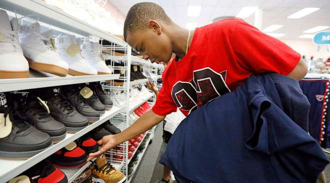 Alex Atkins, 13, looks for a new pair of shoes to go with his new school uniforms at a clothing store