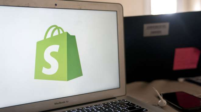 The Shopify logo is displayed on a computer.