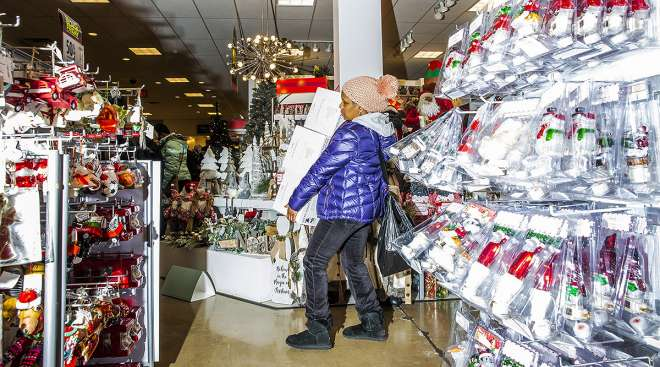 Shopper carrying items in decorated store