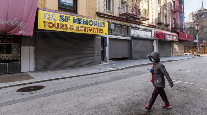 A pedestrian passes closed stores in San Francisco.