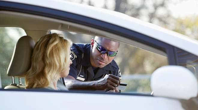 officer writing driver a ticket