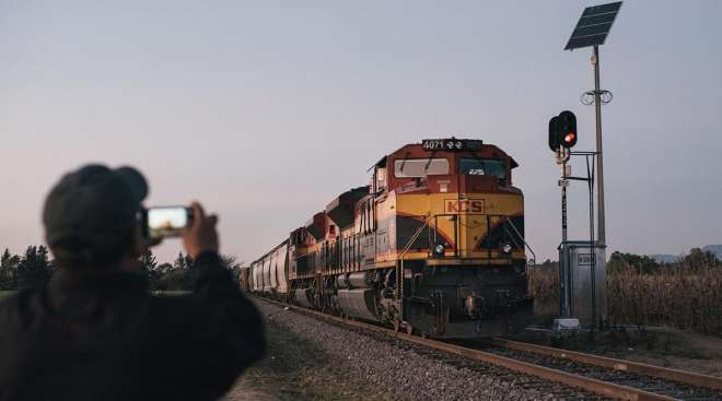 A person photographs a Kansas City Southern freight train in Mexico.
