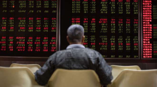 An investor looks at stock price movements on screens at a securities company in Beijing.