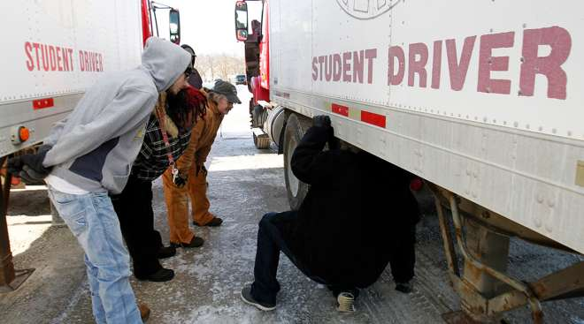 Student drivers look under a truck's trailer
