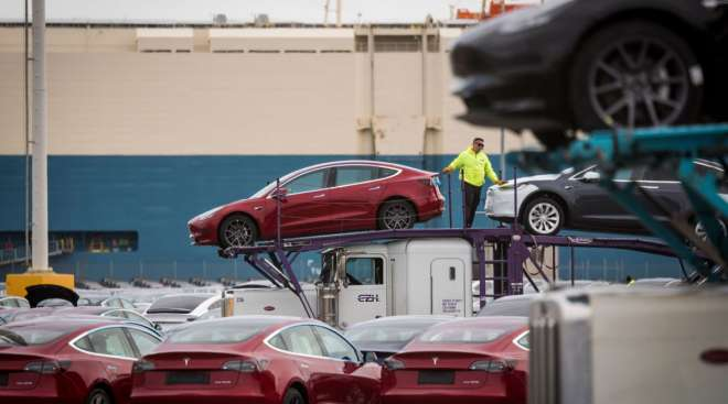 Tesla vehicles are unloaded from car carriers before being shipped from the Port of San Francisco.