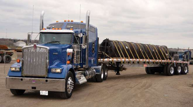 A truck owned by Beemac Trucking carrying a load.