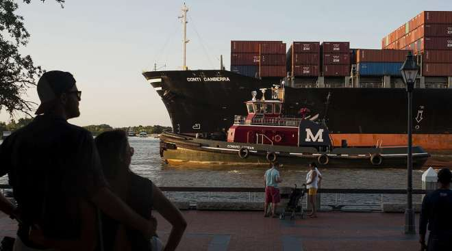 People watch as a cargo ship and tug boat travel into the Port of Savannah. (Ty Wright/Bloomberg News)
