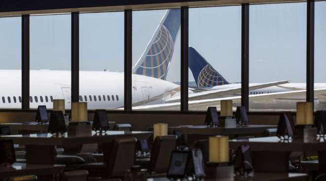 United Airlines planes stand past an empty waiting area for travelers at Newark International Airpor