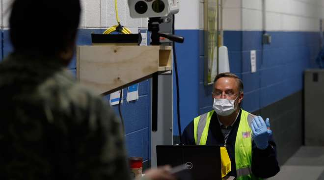 A Ford employee, left, has his temperature checked as he enters a Ford plant in Michigan on May 13.