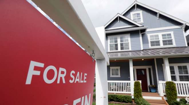 """A """"For Sale"""" sign stands in front of a home in Monroe, Wash., on April 1."""