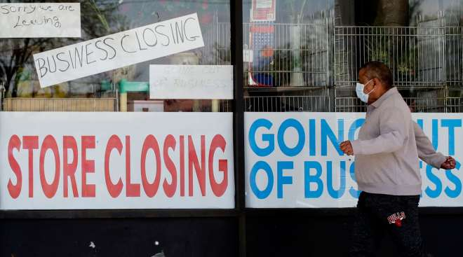 A man looks at signs of a closed store due to COVID-19 in Niles, Ill., on May 21.