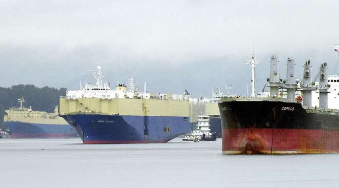 A tugboat maneuvers through waiting freighters on the Columbia River near the Port of Vancouver in Vancouver, Wash.