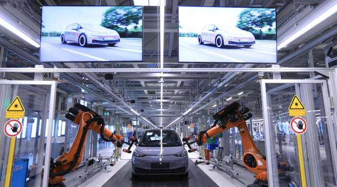 Robotic arms scan the body of a VW ID.3 electric car.