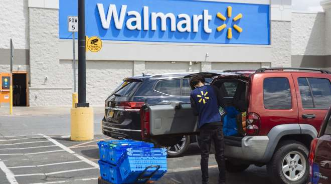 A worker delivers groceries to a customer's vehicle outside a Walmart store in New York on May 15.