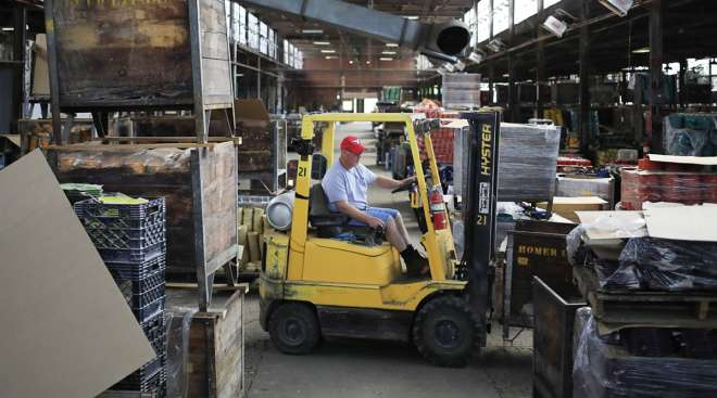 A worker drives a forklift inside a shipping warehouse at the Fiesta Tableware Co. factory in Newell, W.Va.