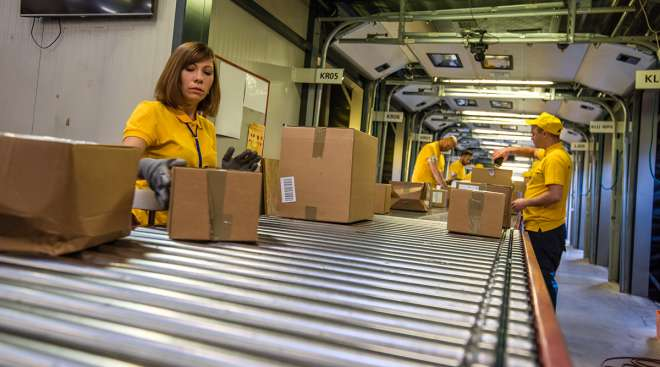 Workers process boxes at a distribution center