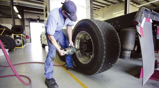 A technician inspects a wide-base tire.