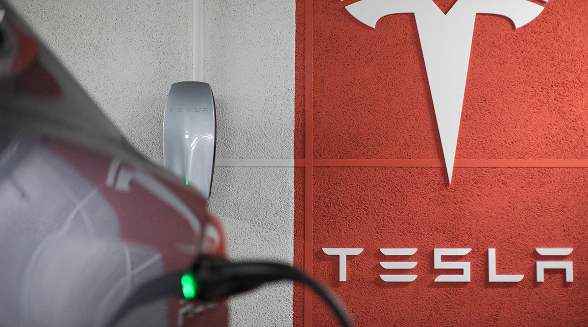A plug sits connected to a Tesla Inc. Model X electric automobile at a charging point in a parking lot in Frankfurt, Germany.