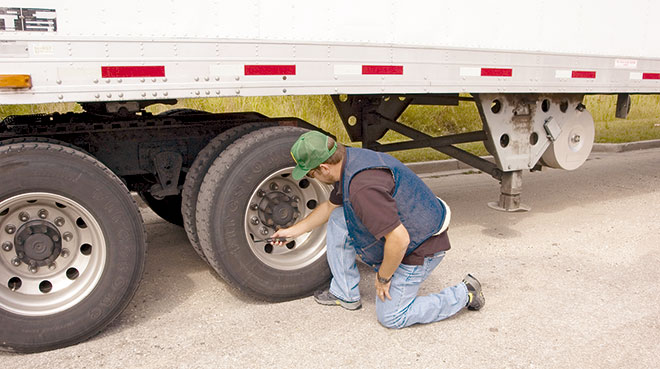 A driver checks the pressure on the tires of his tractor-trailer