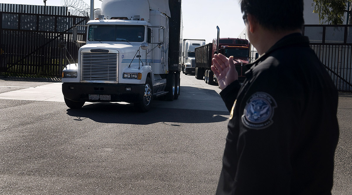 A U.S. Customs and Border Protection official directs trucks heading from the United States to Mexico at the Otay Mesa Port of Entry.