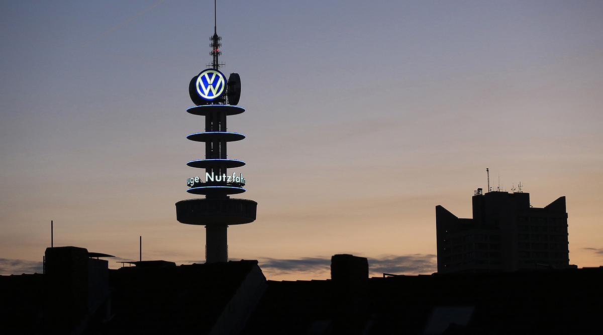 The Volkswagen AG logo sits illuminated on a television transmission mast at dawn in Hannover, Germany.